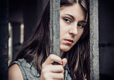 The young woman, behind bar Stock Image