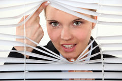 Young woman behind blinds. Young woman behind closed blinds Royalty Free Stock Images