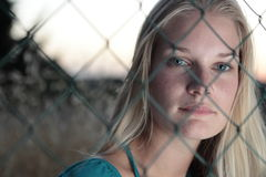 Young woman behind a fence. Portrait of a very pretty young woman behind a fence Royalty Free Stock Photos