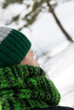 Young woman from behind with a green scarf and a wool cap Stock Images