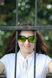 The young woman behind an iron protection. Portrait of the young woman in sun glasses behind an iron protection Stock Photo