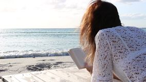 Young woman from behind sitting by the sea looks at the horizon at dawn in the wind, dressed in a white lace dress and white. Young woman from behind lying by stock video footage