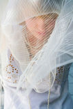 Young woman behind a shawl Royalty Free Stock Photography