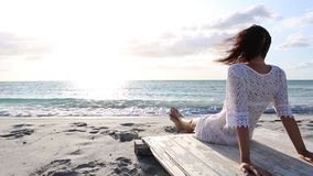 Young woman from behind sitting by the sea looks at the horizon at dawn in the wind, dressed in a white lace dress and white. Underwear and long hair stock video