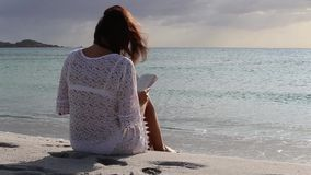 Young woman from behind sitting by the sea looks at the horizon at dawn in the wind, dressed in a white lace dress and white. Underwear and long hair stock video footage