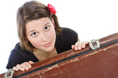 Young woman behind suitcase. Portrait of an attractive young woman looking into camera from behind an old brown suitcase - isolated on white Stock Photo