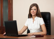 Young woman behind a table with the laptop Stock Photo