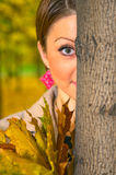 Young woman behind the tree Stock Photo
