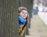 Young woman behind tree Stock Image