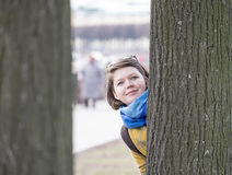Young woman behind tree Royalty Free Stock Photo