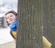 Young woman behind tree Stock Photography