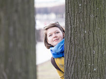 Young woman behind tree Royalty Free Stock Image