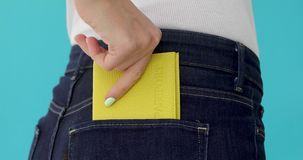 Closeup woman with passport. Young woman behind in worn out jeans and passport in a pocket stock video