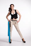 Young woman in beige pants, black vest with blue scarf Royalty Free Stock Photo