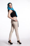 Young woman in beige pants, black vest with blue scarf Stock Photos