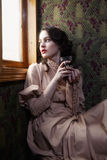 Young woman in beige vintage dress of early 20th century drinkin Stock Photo
