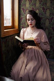 Young woman in beige vintage dress of early 20th century reading Stock Photos