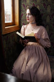 Young woman in beige vintage dress of early 20th century reading Stock Images