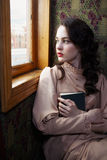 Young woman in beige vintage dress of early 20th century sitting. Near window in coupe of retro railway train Royalty Free Stock Image