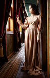 Young woman in beige vintage dress of early 20th century standin. G near window in corridor of retro railway train Royalty Free Stock Photography