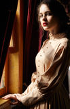 Young woman in beige vintage dress of early 20th century standin. G near window in corridor of retro railway train Royalty Free Stock Photo