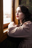 Young woman in beige vintage dress looking trough the  window in Royalty Free Stock Image