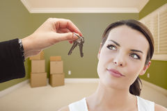 Young Woman Being Handed Keys in Empty Room with Boxes Royalty Free Stock Photography