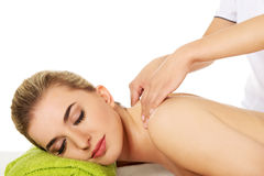 Young woman is being massaged. Royalty Free Stock Image