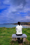 Young woman on bench. Young woman sitting, reflecting on a bench overlooking ocean stock images
