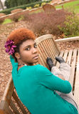 Young Woman on Bench. A portrait of a young black woman sitting on a bench and staring over her shoulder at the viewer with piercing eyes Royalty Free Stock Photo