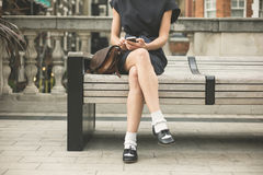 Young woman on bench in city with phone Stock Image