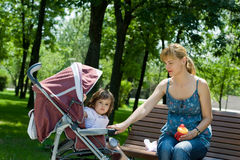 Young woman on bench with a pram Royalty Free Stock Image