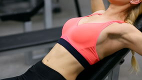 Young woman bench pressing with dumbbells in the gym, working triceps and chest stock video