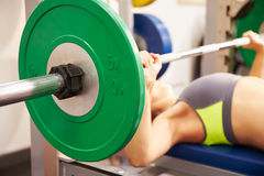 Young woman bench pressing weights at gym, focus on barbells Stock Photos