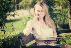 Young woman on bench reading book Royalty Free Stock Image