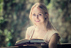Young woman on bench reading book Stock Image