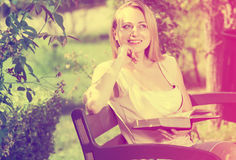Young woman on bench reading book Royalty Free Stock Photography