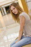 Young woman on bench in shopping centre Royalty Free Stock Photography