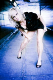 Young woman bending. Young blond woman in short, stylish dress, bending over.  Color modified Stock Images
