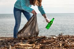 A young woman bends down to collect a dirty glass bottle. Cleaning and environmental protection.  stock photos