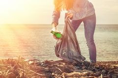 A young woman bends down to collect a dirty glass bottle. Cleaning and environmental protection. Light from the right top corner.  royalty free stock photos