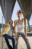 Young woman beneath overpasses, friend by fence, smiling, portrait, low angle view Stock Photos