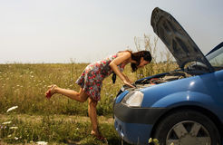 Young woman bent over a car. Young woman bent over the engine of a broken car Stock Image