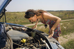 Young woman bent over engine. Young woman bent over the engine of a broken car Royalty Free Stock Photography