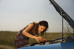 Young woman bent over engine. Young woman bent over the engine of a broken car trying to fix it Stock Images
