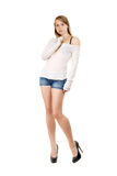 Young woman with bewildered look. Young woman wearing blue jeans shorts, white blouse and black shoes with bewildered look. Isolated Stock Photos