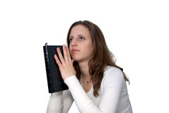 Young Woman with Bible praying. Isolation of a Young Woman holding a Bible in a praying posture stock images