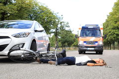 Young Woman with bicycle accident and comming ambulance car Stock Images