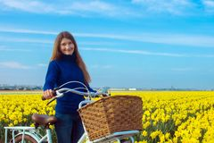 Young woman with bicycle at the background of blossoming spring Stock Image