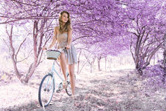 Young woman on bicycle in fantasy pink forest Stock Photos